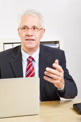 Geschäftsmann mit Laptop am Schreibtisch