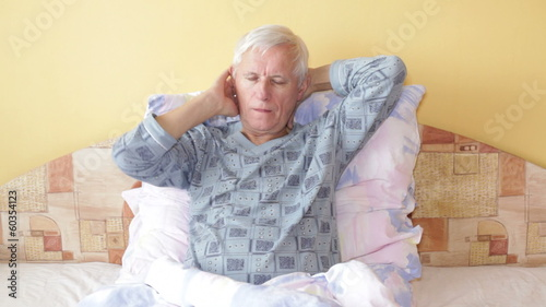 Sick senior man in bed with sore throat.