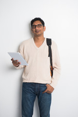 casual indian male student on a sweater and tablet