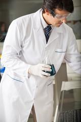 Scientist Examining Green Solution In Flask