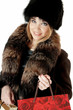 Elegant stylish woman in fur with shopping gift bags, against wh