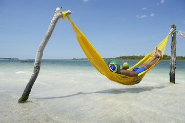 Brazilian Man Relaxing in Beach Hammock with Drinking Coconut