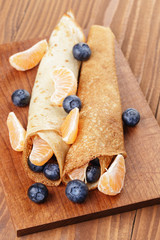 homemade blinis or crepes with blueberries and tangerines
