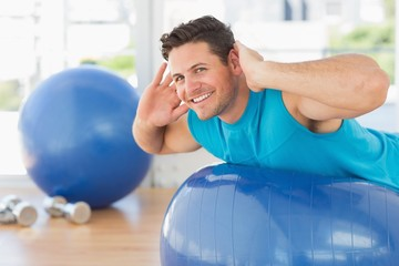 Young man exercising on fitness ball at gym