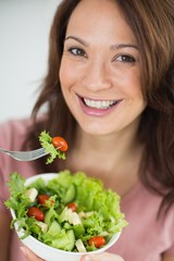Close-up of smiling woman with bowl of salad