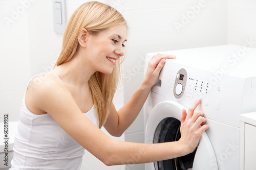 Young beautiful woman using a washing machine