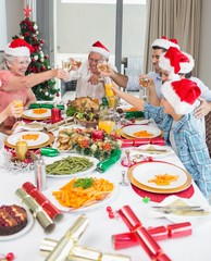 Family in santa's hats toasting wine glasses at dining table