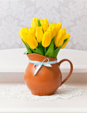 yellow tulips in vase with blue bow on white table