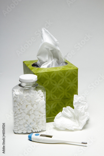 Tissue with thermometer and bottle of aspirin, vertical