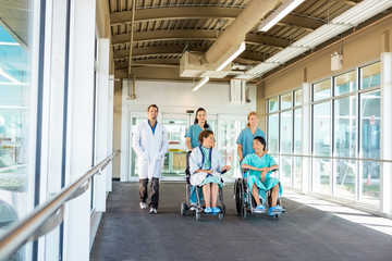 Medical Team With Patients On Wheelchairs At Hospital Corridor