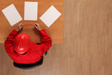 overhead view of worker in red uniform, hardhat browsing papers