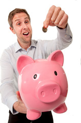 pink piggy bank with man inserting coins into it.