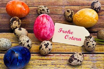 bunte Ostereier zwischen Wachteleiern mit Anhänger, Frohe Ostern