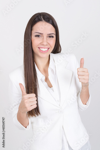 Happy businesswoman in white showing thumbs up