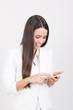 Happy businesswoman in white using smartphone