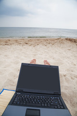 Sitting with laptop on sandy sea beach