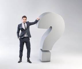 Elegant young man leaning against the question mark