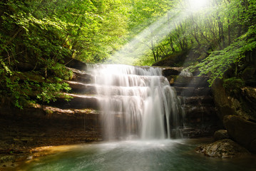 waterfall illuminated by sun beam