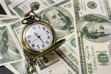 Pocket watch and dollar bills. Time makes money