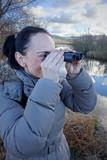 Woman looking through binoculars birdwatching on wetland poster