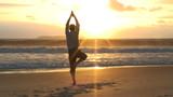 Geschäftsmann macht Yoga am Strand bei Sonnenaufgang.