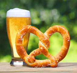Beer Glass with German Pretzel on Wooden Table over Nature Green