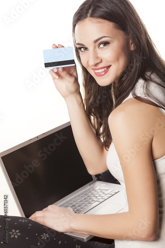 smiling girl buys online on a computer and showing a credit card
