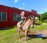 child riding a miniature donkey