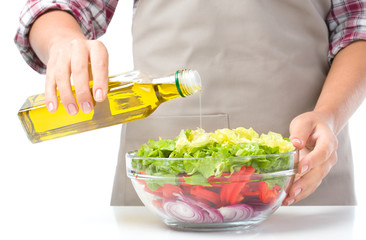 Cook is pouring olive oil into salad