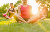 horizontal of a group of women doing yoga at sunset with flare
