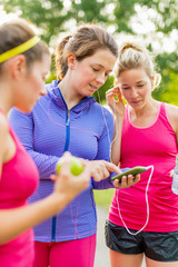 Group of female joggers laughing while using a smart phone