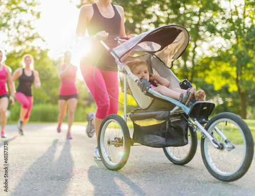 Papiers peints Ecole de Danse Woman pushing her toddler while running in nature with friends