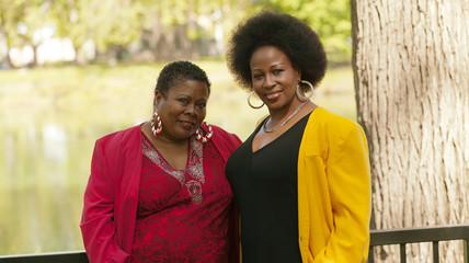 Two Older Black Women Outdoor Portrait Red Yellow