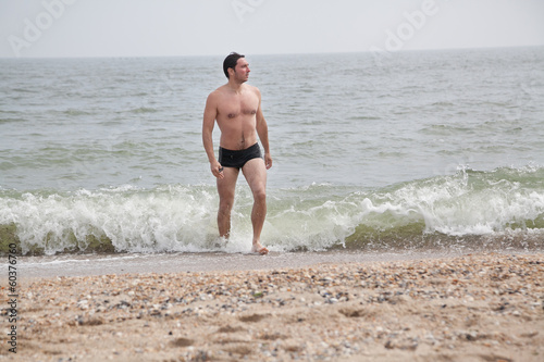 Young man in shorts walking out of the sea