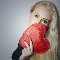 Happy Young Blond Woman Holding Red Heart. Valentine's Day