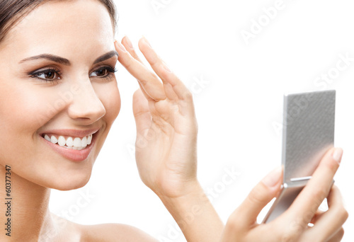 Woman looking at mirror, isolated over white