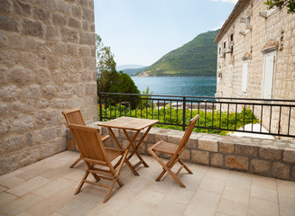 Wooden chairs and table on open seaside terrace