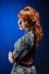 Portrait of red-haired model posing in dress