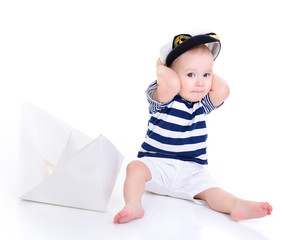 cute baby boy sitting in captain cap with ship of paper - sailor