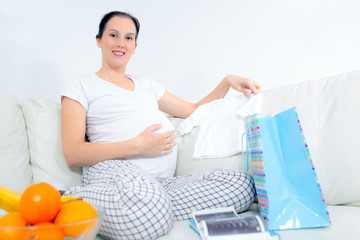 Pregnant woman hands holding white baby T-shirt