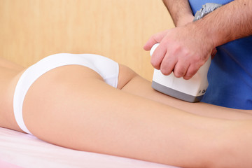 young woman getting anticellulite and anti fat therapy in beauty