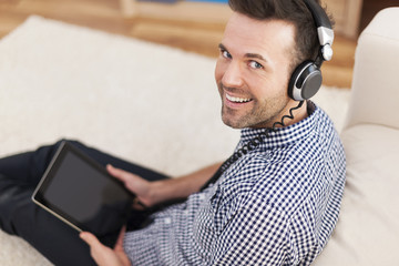 Portrait of smiling man listening music at home