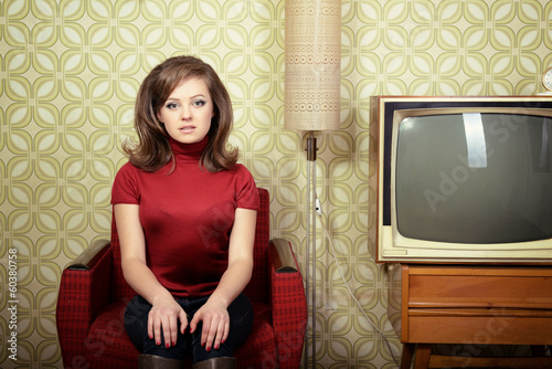 art portrait of young woman sitting on chair and looking at came