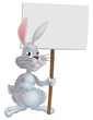 White Easter bunny holding sign