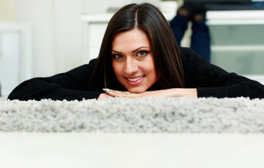 Middle-aged happy smiling woman lying on the carpet at home