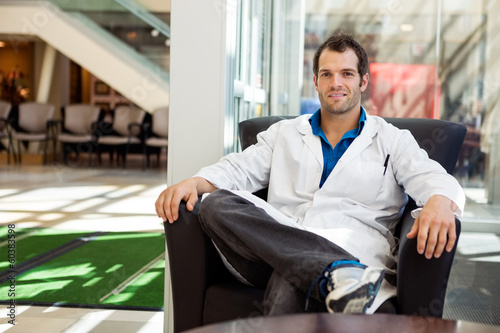 Confident Male Doctor Sitting On Chair