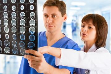Two doctors with tomogram in hospital's corridor
