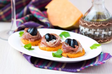 Canape appetizer of pumpkin, jamon ham, black olives, cheese