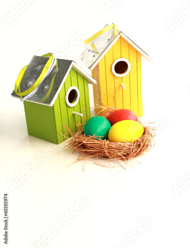 Colorful Easter eggs in a nest with birdhouses on background