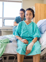 Nurse Examining Patient's Back With Stethoscope On Hospital Bed